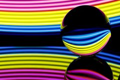 Crystal ball with colorful neon lighting behind royalty free stock photos