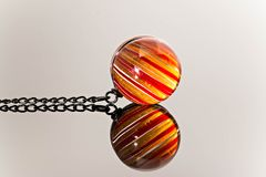 Colorful marble, Crystal ball, glass ball, marble mirror reflection. Close up macro glass ball, red and yellow colored crystal marble, stripes ball with black Stock Image