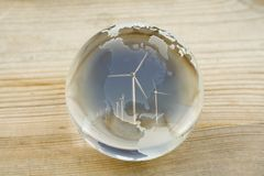Crystal ball globe with wind farm over North and Central America. (consisting of several wind turbines and blue sky) on a pine wood surface Royalty Free Stock Photo