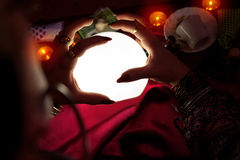 Crystal ball with hands of fortune teller woman. Above it Royalty Free Stock Images