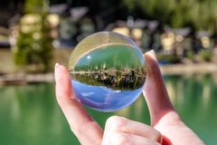 Crystal ball in hands. Reflection of water. Resort Hrabovo near town Ružomberok, Slovakia at background royalty free stock photography