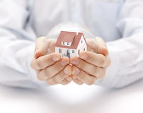 Crystal ball with house in hands Stock Photos