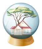 A crystal ball with a house and a tree inside Stock Photo