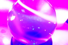 Crystal ball on pedestal in pink. Close up of crystal ball reflecting light on pedestal in pink Royalty Free Stock Photos