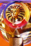 Crystal ball and Pharaoh. Ball of crystal glass showing the reflection of a pharaoh statuette in front of coloured background stock photography
