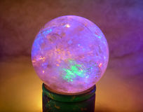 Crystal Ball. Quartz crystal ball sitting on a wood napkin holder and lit with Christmas lights Stock Image
