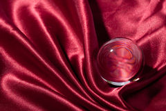 Crystal ball on red silk textile Stock Images