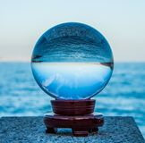 Crystal ball reflecting a blue ocean. A hand is holding a crystal ball that is reflecting a blue ocean. Blue sky in the background. The location is Arenzano royalty free stock photography