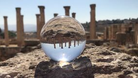 Crystal ball reflection against ancient ruins of roman city, columns, hand holding