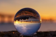 Crystal Ball Reflection on the seashore in sunrise light. Reflection of a bridge in the crystal ball.  stock images