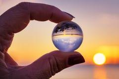 Crystal Ball Reflection sulla spiaggia alla luce di alba Sfera di cristallo in una mano del ` s della donna Fotografia Stock