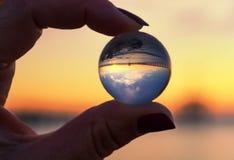 Crystal Ball Reflection sulla spiaggia alla luce di alba Sfera di cristallo in una mano del ` s della donna Fotografie Stock Libere da Diritti