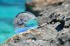 Crystal ball on rocks Royalty Free Stock Photos