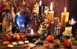 Crystal ball with runes, black candle and witch magic bottle. Wicca, esoteric, Halloween and occult background with vintage magic objects for mystic rituals stock photography