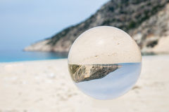Crystal ball on sandy greek beach Royalty Free Stock Image