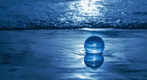 Crystal ball in the sea. Crystal ball in the blue sea with reflection Stock Photo