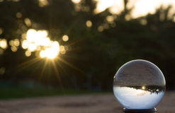 Crystal ball with sun flare and beach reflection. Crystal ball with sunset, bokeh and beach reflection Royalty Free Stock Image