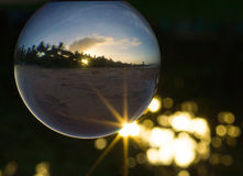Crystal ball with sun flare, bokeh and sunset. Crystal ball with sunset and beach reflection Stock Images