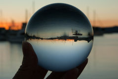 Crystal ball with sunset. Holding crystal ball with boats and sunset reflected Stock Photography