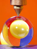Crystal ball under point. Ball of crystal in a press, having behind it a highly reflective ball of yellow glass, both surrounded with coloured backgrounds royalty free stock images