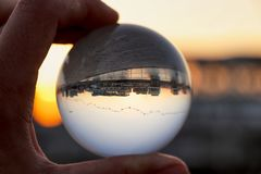 Crystal ball wih recletion of Limassol´s harbour at sunset. Glass/Lens ball holding in hand with golden city lights and sea in. The background reflecting the royalty free stock photos