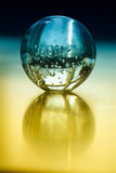 A crystal ball on a yellow table. A clear crystal ball on a yellow table with a blue background Stock Image