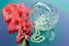 Crystal basket in the shape of a ball. Pearls and beautiful gladiolus Stock Photography