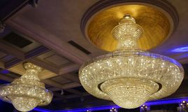 Crystal big chandeliers. Enclosed by the blue border Stock Photography