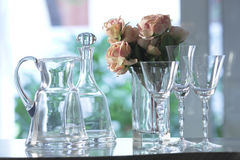 Crystal carafe, bottle and glasses. With flowers, interiors day Stock Photos