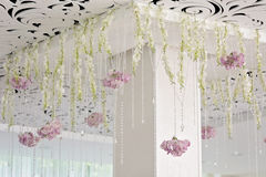 Crystal chains hang art decor wedding ceiling close. Crystal chain hanging from the ceiling, along with flowers hydrangeas and delphinium white. white columns Stock Photography