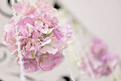 Crystal chains hang art decor wedding ceiling close. Crystal chain hanging from the ceiling, along with flowers hydrangeas and delphinium white. white columns Royalty Free Stock Photos