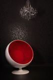 Crystal chandelier with candles and red ball-chair Stock Photos