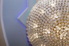 Close-up of beautiful crystal chandelier round shape hanging from the ceiling in the interior. Crystal chandelier close-up. Richly theatrical chandelier in a stock images
