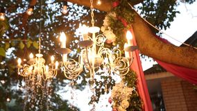 Crystal chandelier with flowers and garlands shines on wedding ceremony and party. Holiday decor, rustic style. stock video
