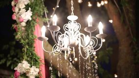 Crystal chandelier with flowers and garlands shines on wedding ceremony and party. Holiday decor, rustic style. stock footage