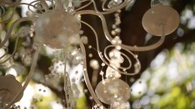 Crystal chandelier with flowers and garlands on wedding ceremony. Holiday decor, rustic style. stock video