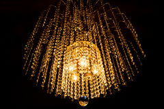 A crystal chandelier glows with golden light Royalty Free Stock Images