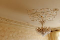 Crystal chandelier with gold on a white ceiling with retro stucco stock photos