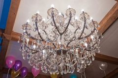 Crystal chandelier hanging on the ceiling . Large crystal chandelier with pendants in ceiling. Luxurious round lamp in their glass royalty free stock photos