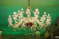 Old Crystal chandelier on green background. Old crystal chandelier in the ballroom, on green background stock image