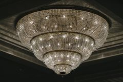 Crystal chandelier. Shines hanging from the ceiling in the hotel hall stock image