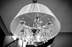 A crystal chandelier with a white shade. Of black-and-white photo stock photos