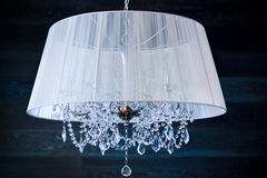 A crystal chandelier with a white shade. On a dark background royalty free stock photos