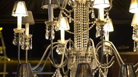 Crystal chandelier with yellow garlands on the dark background stock video footage