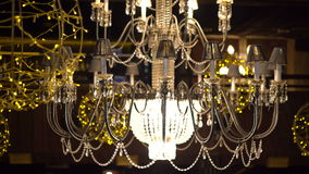 Crystal chandelier with yellow garlands on the dark background 4K stock video footage