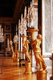 Crystal chandeliers and gold statues in Versailles. Crystal chandeliers and golden statues in mirror room in Versailles castle near Paris, France, Europe Royalty Free Stock Photos