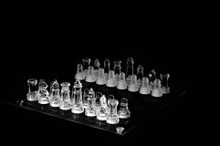 Crystal  chess board and figures. Crystal chess pieces on black background Royalty Free Stock Photos