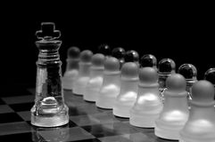 Crystal  chess board and figures. Crystal shess fugures on row against the king,on black background Royalty Free Stock Image
