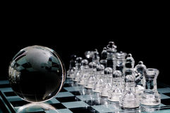 Crystal  chess board and figures. Crystal shess fugures on row against the world globe ,on black background Stock Image