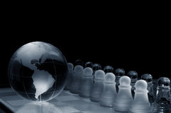 Crystal  chess board and figures. Crystal shess fugures on row against the world globe ,on black background Royalty Free Stock Images